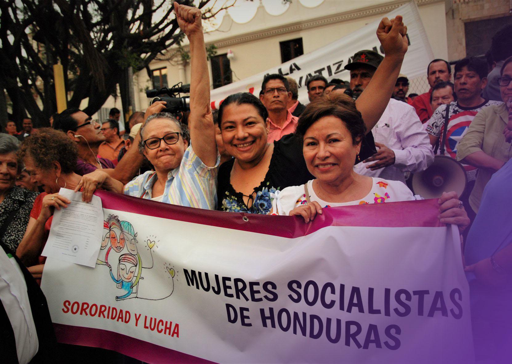 Yamileth Gonzáles al centro de la foto, junto a sus compañeras en una manifestación, sosteniendo una pancarta de las Mujeres Socialistas de Honduras, por sororidad y lucha.
